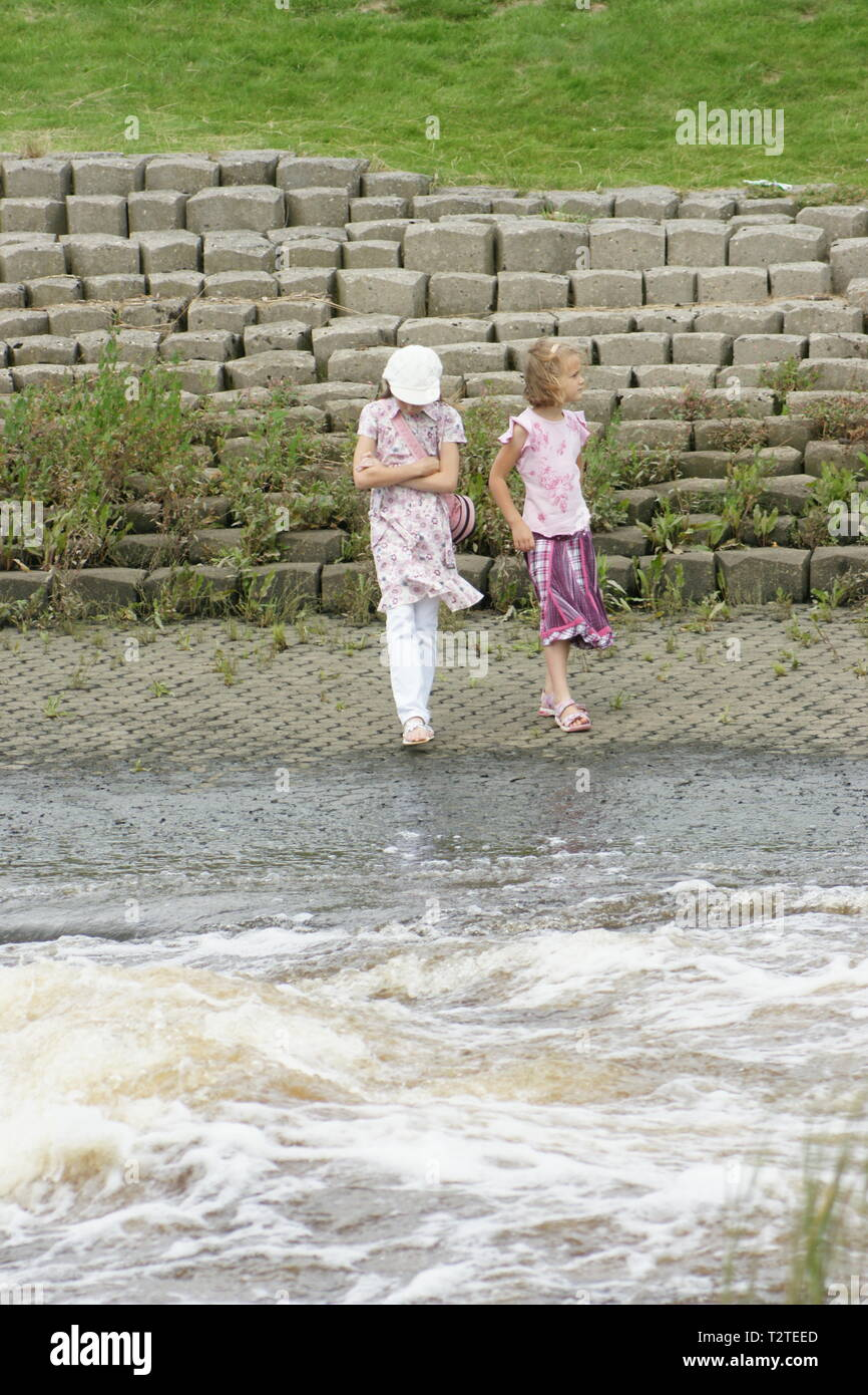 young girls playing near fast moving river, water safety code Stock Photo
