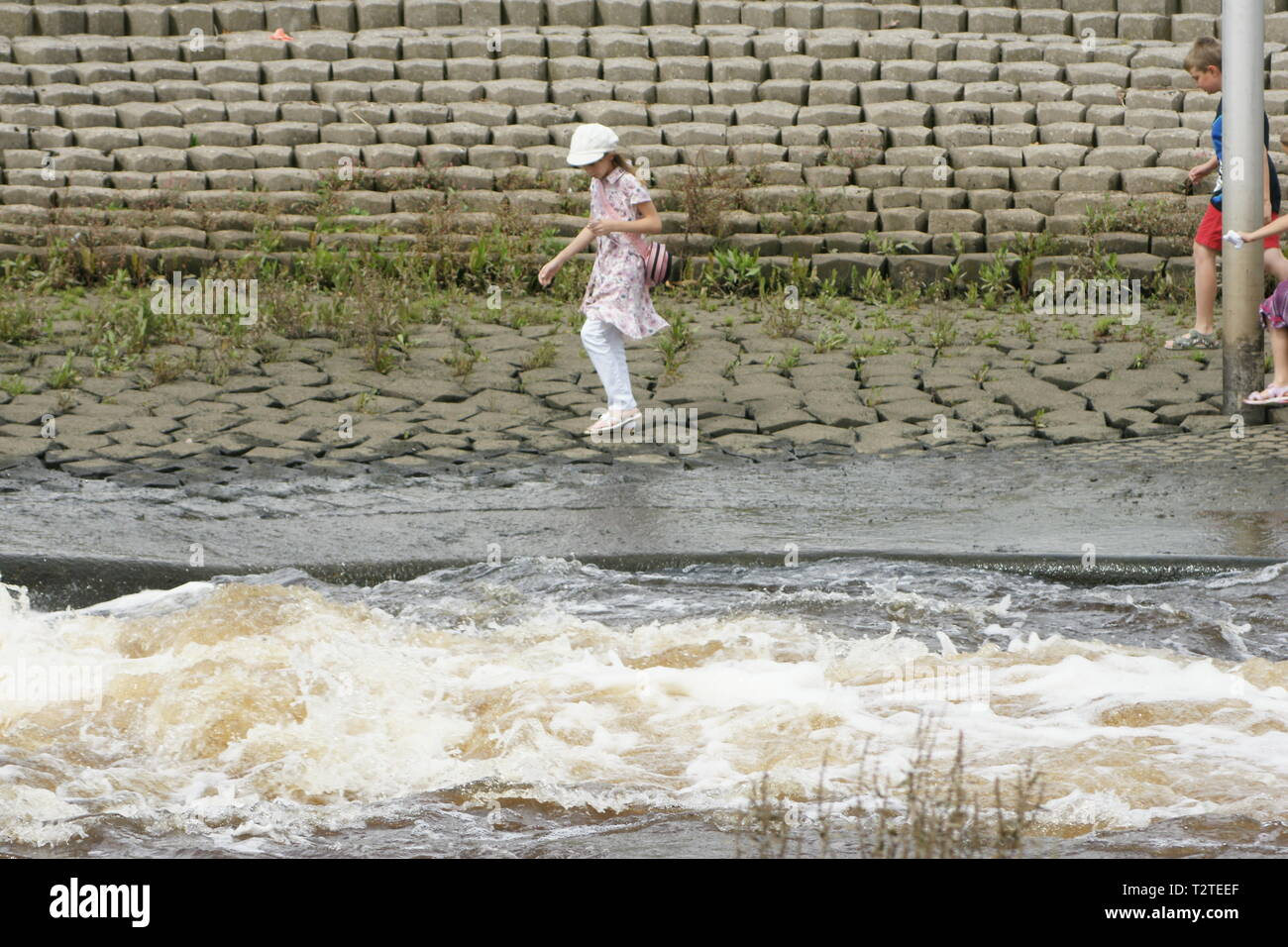 children walking near fast moving river, water safety code Stock Photo