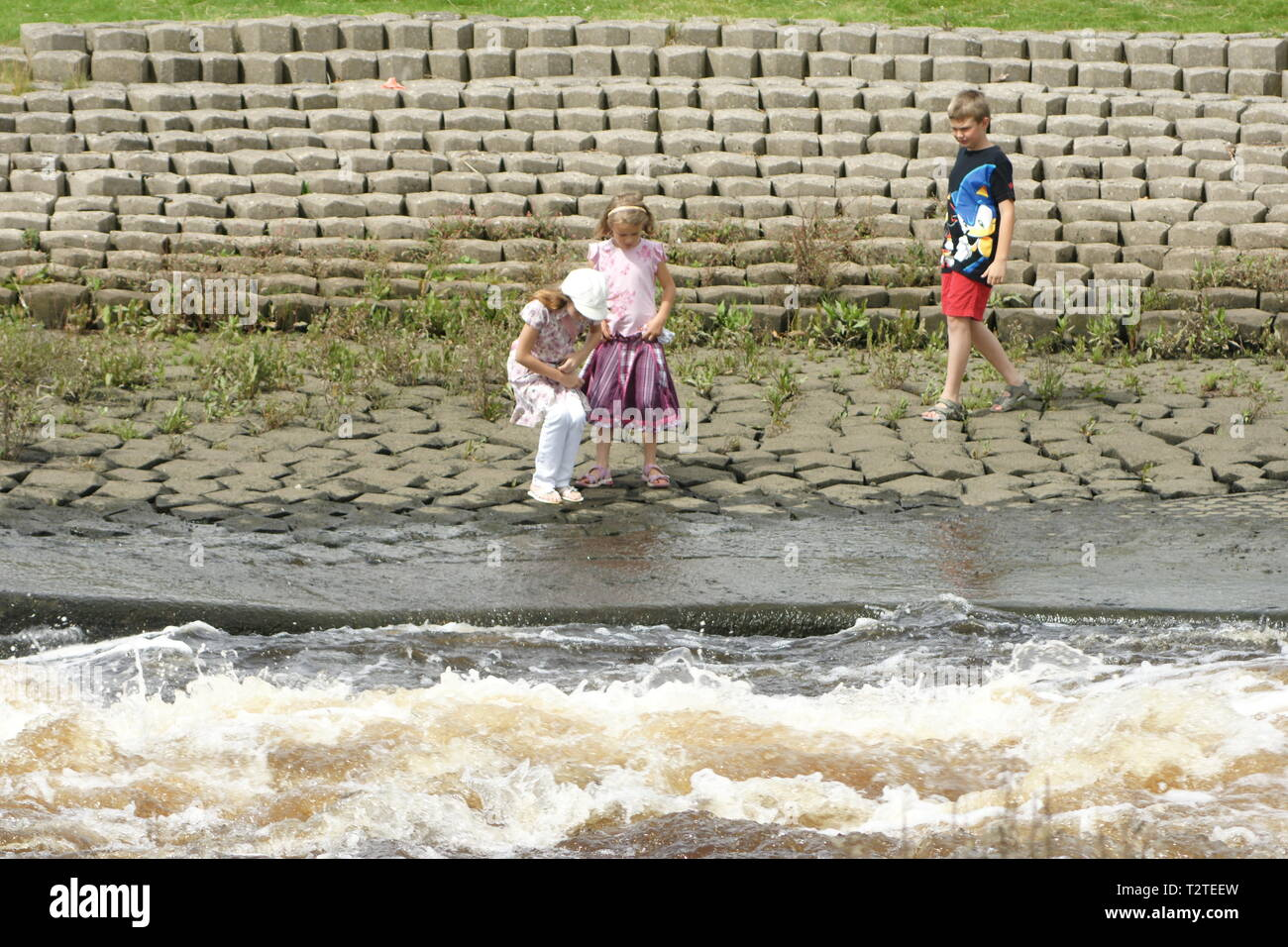 children playing near fast moving river, water safety code Stock Photo