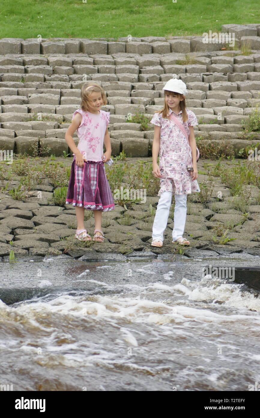girls playing near fast moving river, water safety, Stock Photo