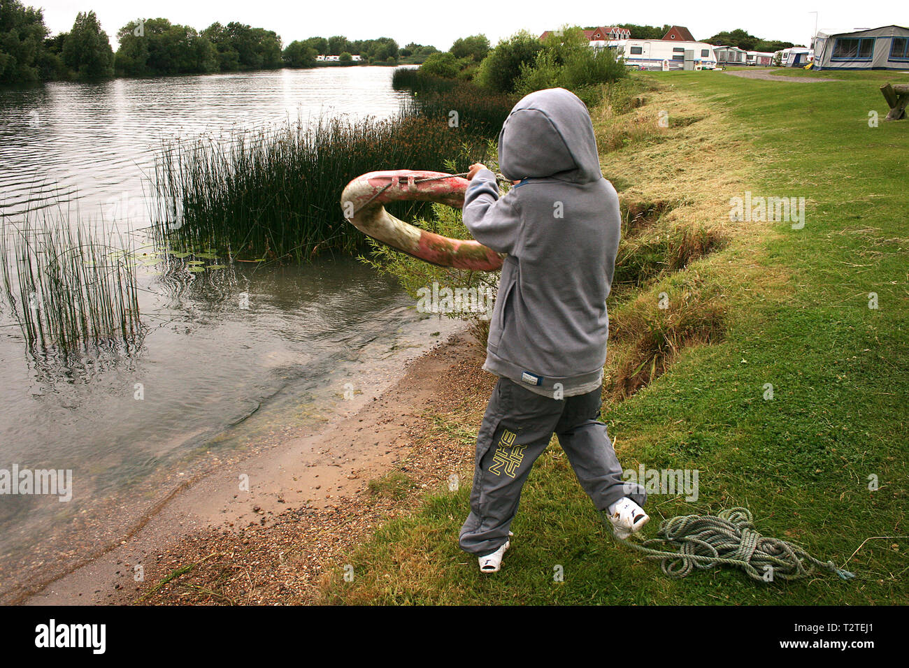 boy throwing lifebuoy to friend in river Stock Photo