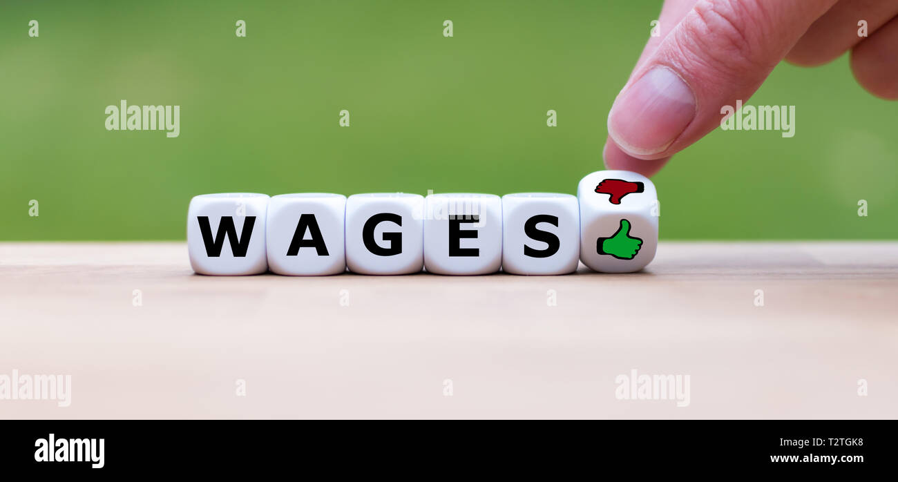 Symbol about job satisfaction. Dice form the word 'wages' and a hand turns a dice and changes a thumbs down symbol to a thumbs up symbol. - Stock Image