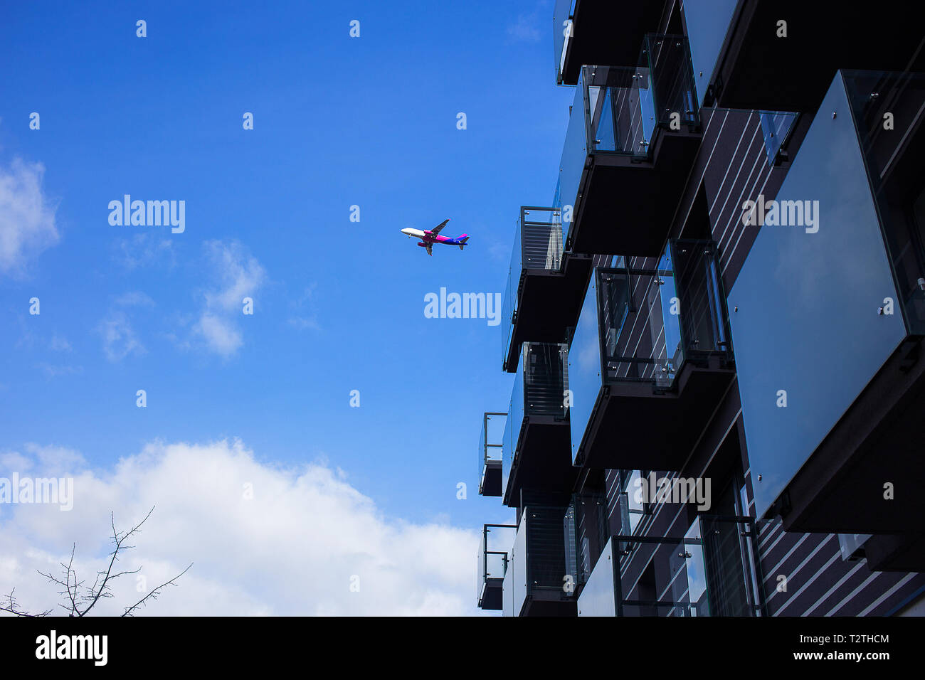 Poznan - Poland / March 16 2019, Plane is flying over new luxury apartment building during one of the last flights, Hungarian budget airlines Wizz Air Stock Photo