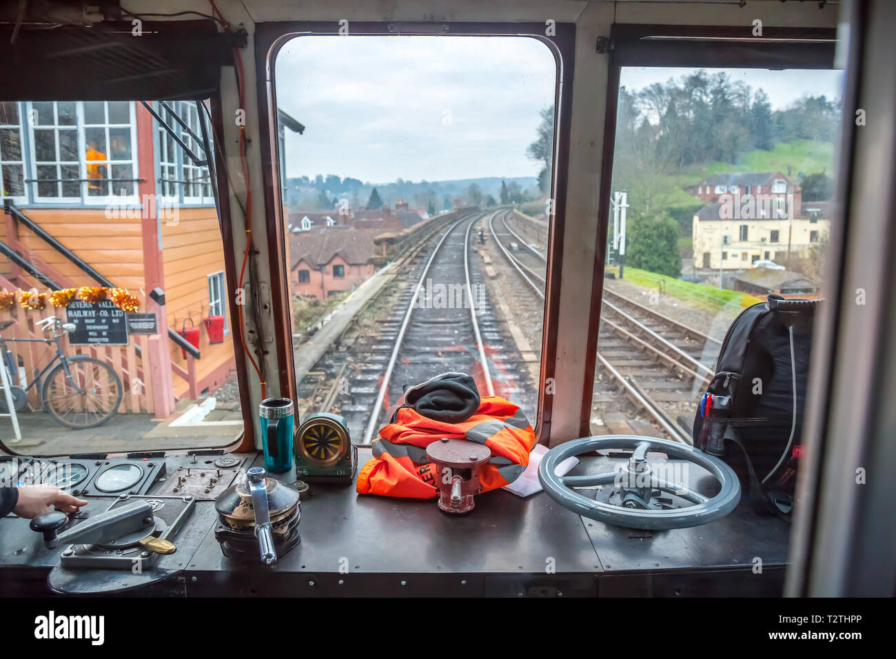 At the controls. Train driver's view through front window of moving diesel train on heritage railway line. Leaving vintage station. Stock Photo