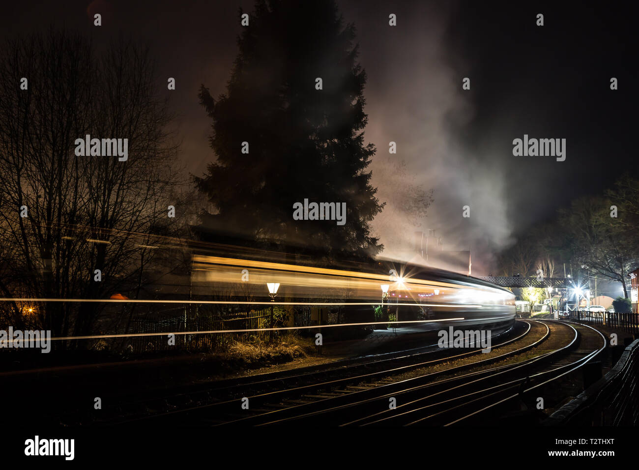 Atmospheric, moody night time capture of moving steam train carriages travelling through vintage railway station at night. Fast motion blur effect. - Stock Image