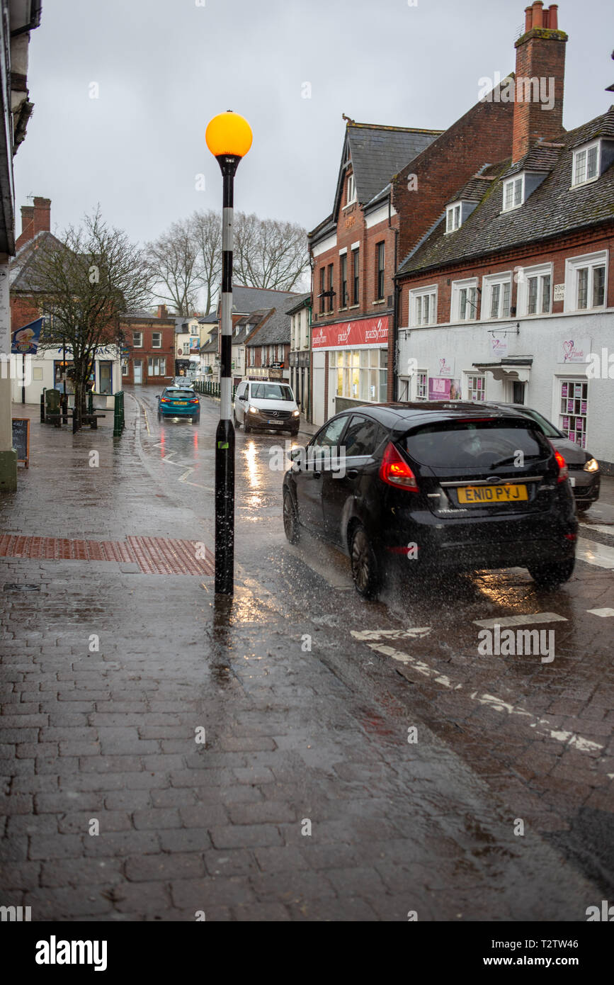 Fordingbridge, New Forest, Hampshire, UK, 4th April 2019, Weather: Torrential rain from April showers in the afternoon. Spray caused by passing traffic driving through deep puddles makes the narrow town centre pavements places to avoid. Credit: Paul Biggins/Alamy Live News Stock Photo