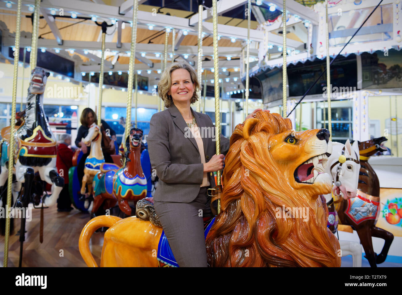 Garden City, New York, USA. 9th Mar, 2019. LAURA CURRAN, the Nassau County Executive, rides Nunley's Carousel carved wood lion during mural unveiling ceremony of Nunley's Carousel horse. Event was held at historic Nunley's Carousel in its Pavilion on Museum Row, Long Island. Credit: Ann Parry/ZUMA Wire/Alamy Live News Stock Photo