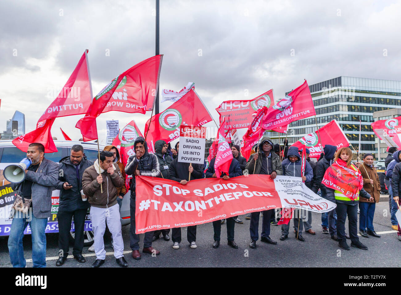 London, UK, 04th April 2019. Minicab drivers block the road on London Bridge protesting against the congestion change on private hire minicabs.  The demonstrators hold and wave flags and placards of UPHD (United Prive Hire Drivers) and IWGB (Independent Workers Union of Great Britain). Credit: Graham Prentice/Alamy Live News Stock Photo