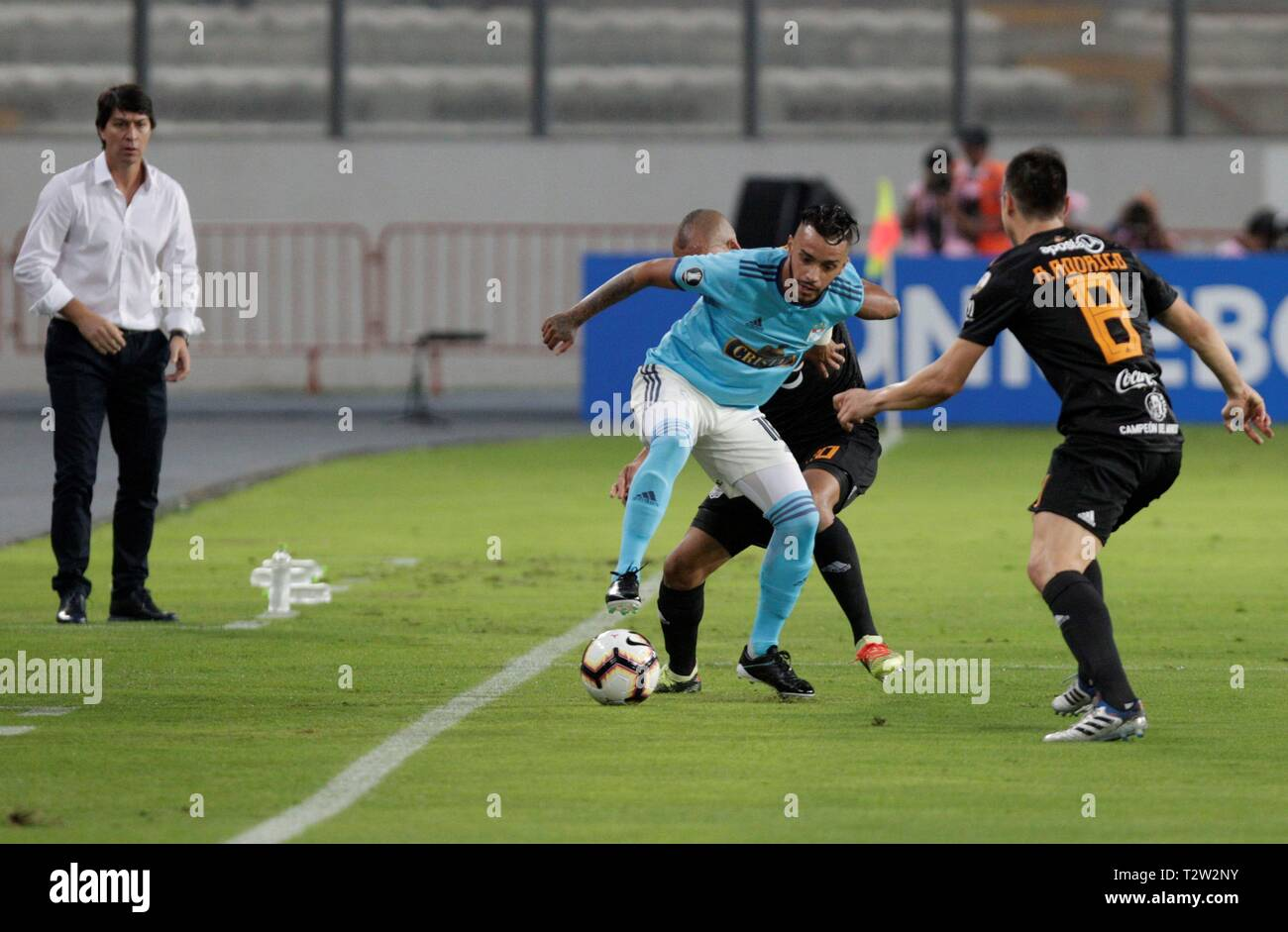 Lima, Peru. 05th Apr, 2019. Sporting Cristal's Patricio Arce (C) vies for the ball Olimpia's players during a game of the Copa Libertadores, at the National Stadium un Lima, Peru, 4 April 2019. Credit: Stringer/EFE/Alamy Live News - Stock Image