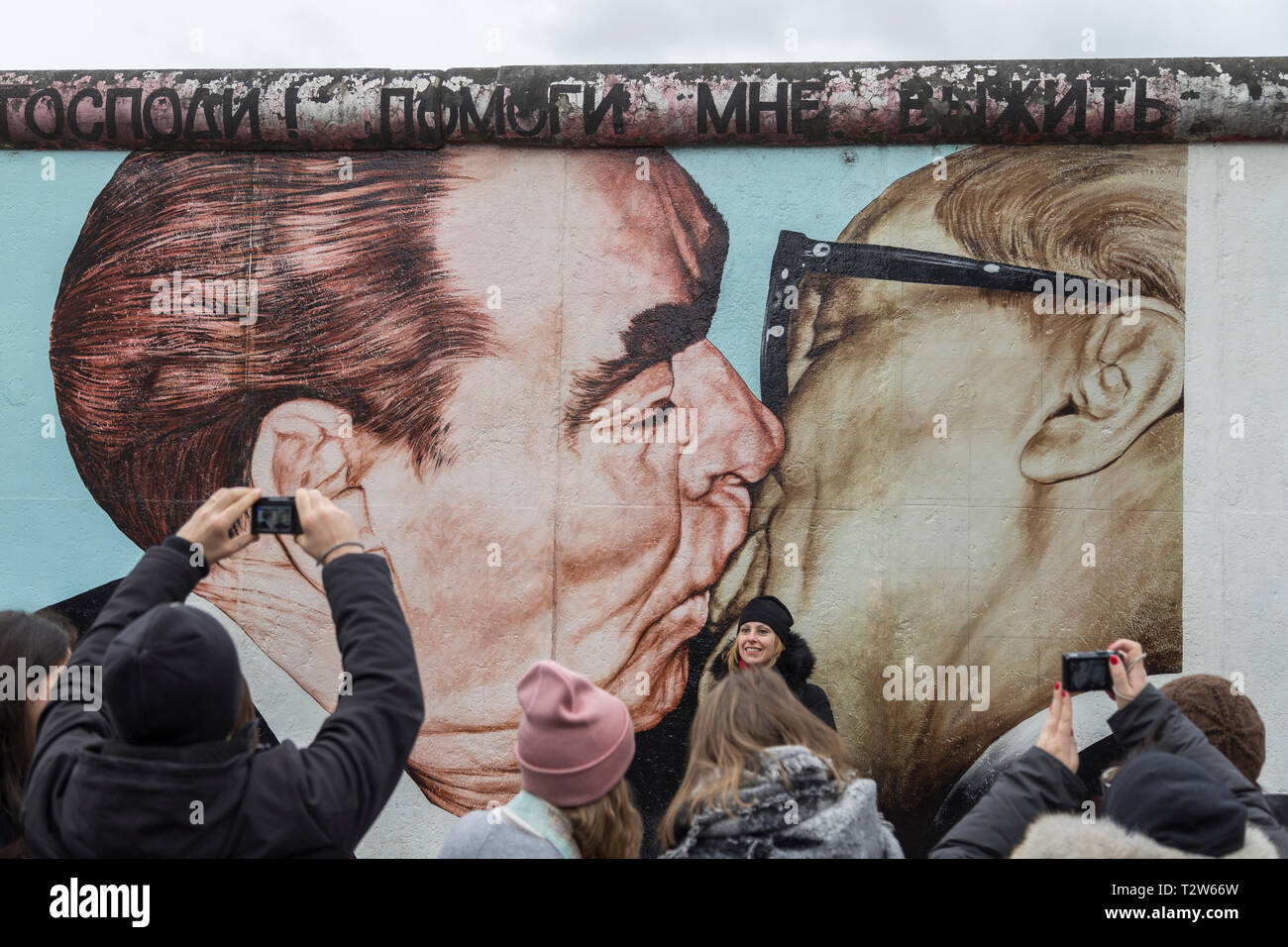 """Tourists at the """"My God, Help Me to Survive This Deadly Love"""" (or """"Fraternal Kiss"""") mural painting by Dmitri Vrubel at the East Side Gallery in Berlin. Stock Photo"""
