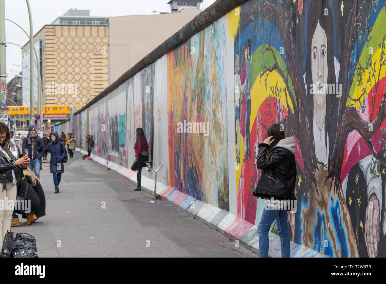 Tourists walking by, taking photos and posing in front of murals at the East Side Gallery, section of the Berlin Wall in Berlin, Germany. Stock Photo