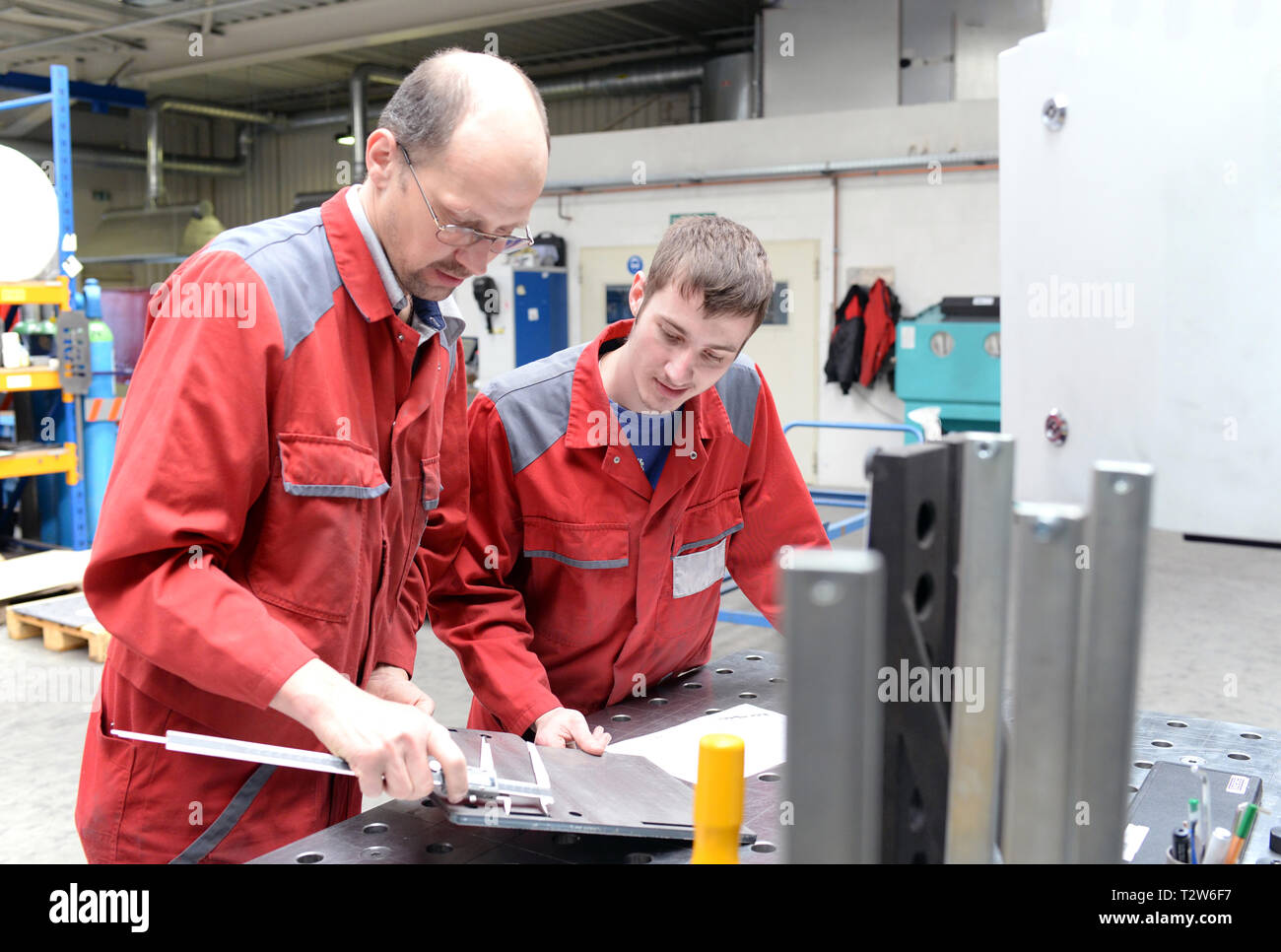 apprentice and trainer in a metalworking company - apprenticeship in the trade - Stock Image