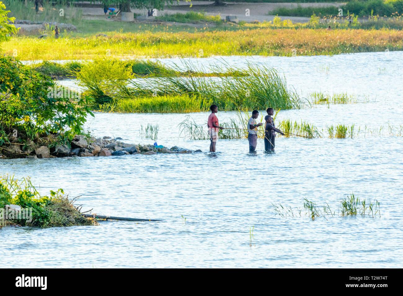 Three Malawian boys fishing with rods in lake Malawi Stock Photo