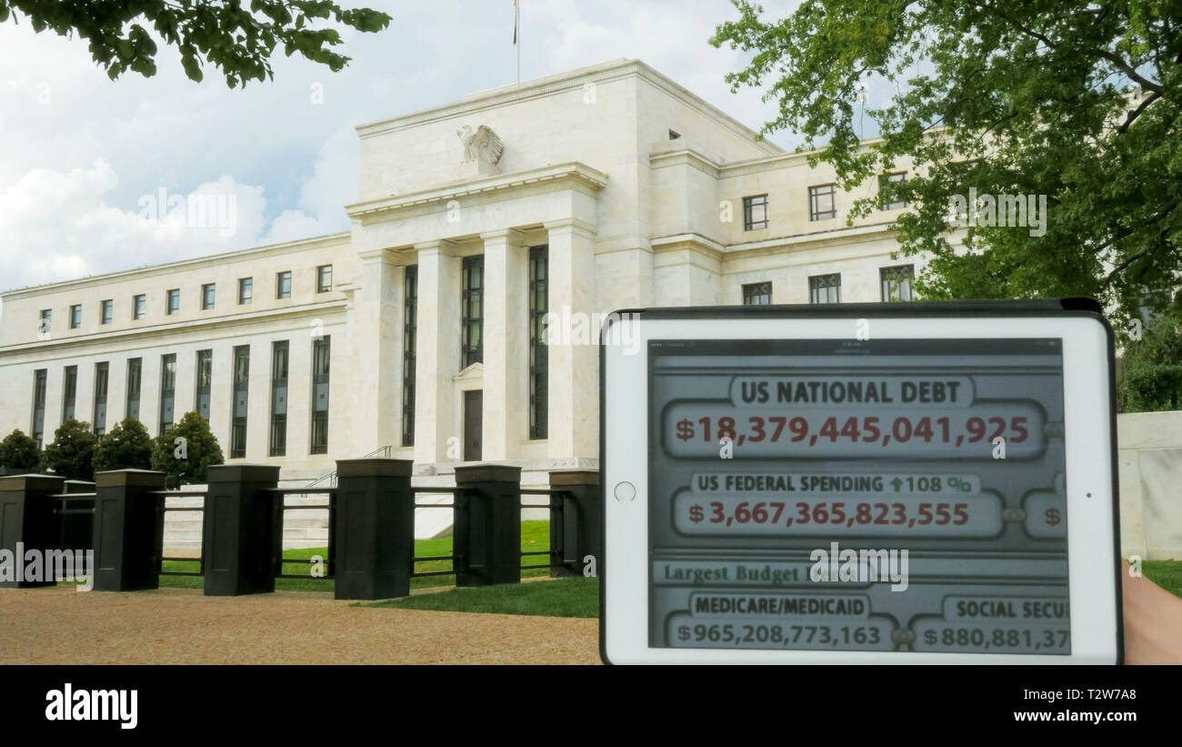 a debt clock and the exterior of the federal reserve building in washington, dc - Stock Image
