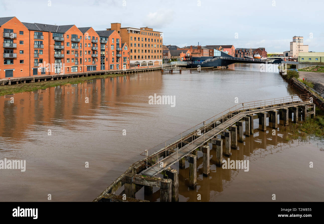 River Hull flanked by modern flats and offices, and derelict causeway  and Scale Lane bridge in Hull, Yorkshire, UK. - Stock Image