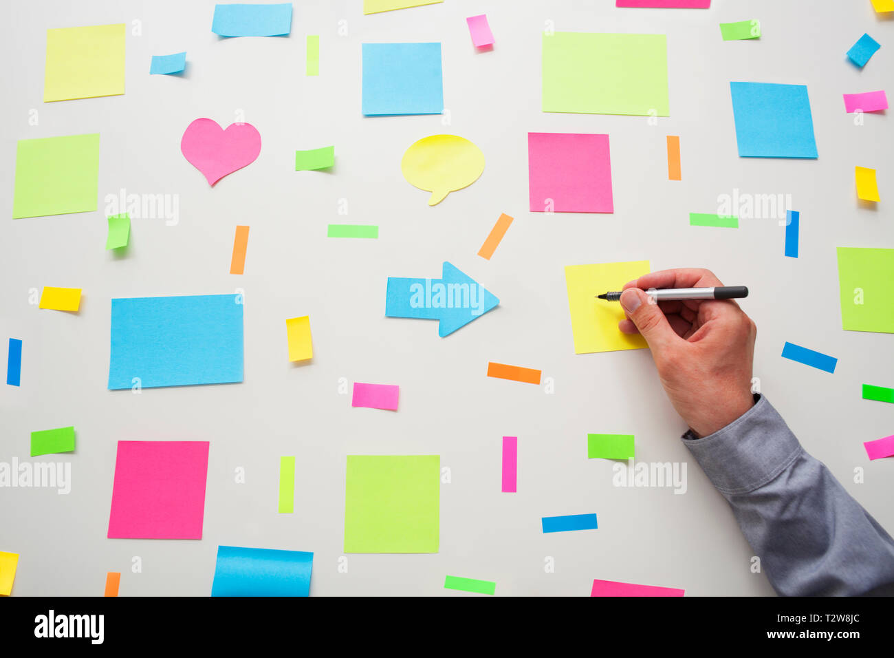Caucasian businessman writing on a post it note surround by post it notes on a wall - Stock Image