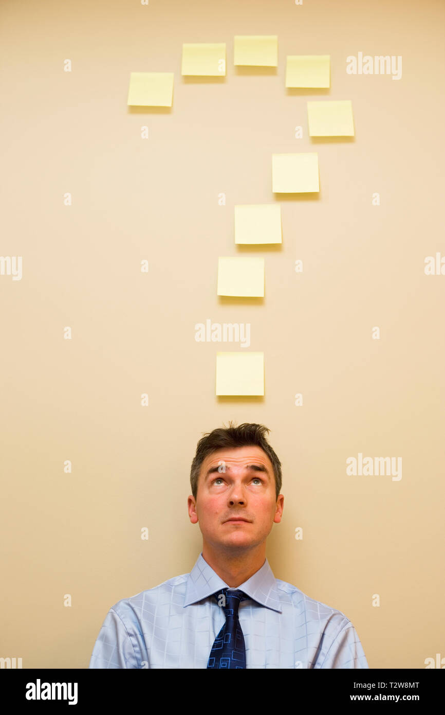 Caucasian middle aged businessman under post it notes in the shape of a question mark - Stock Image