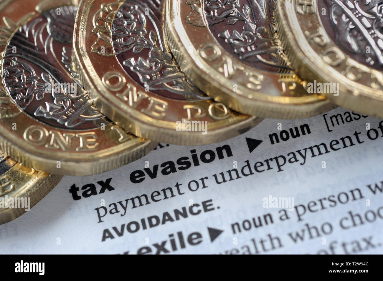 DICTIONARY DEFINITION OF TAX EVASION WITH ONE POUND COINS RE PENSIONS TAX HMRC ETC UK - Stock Image