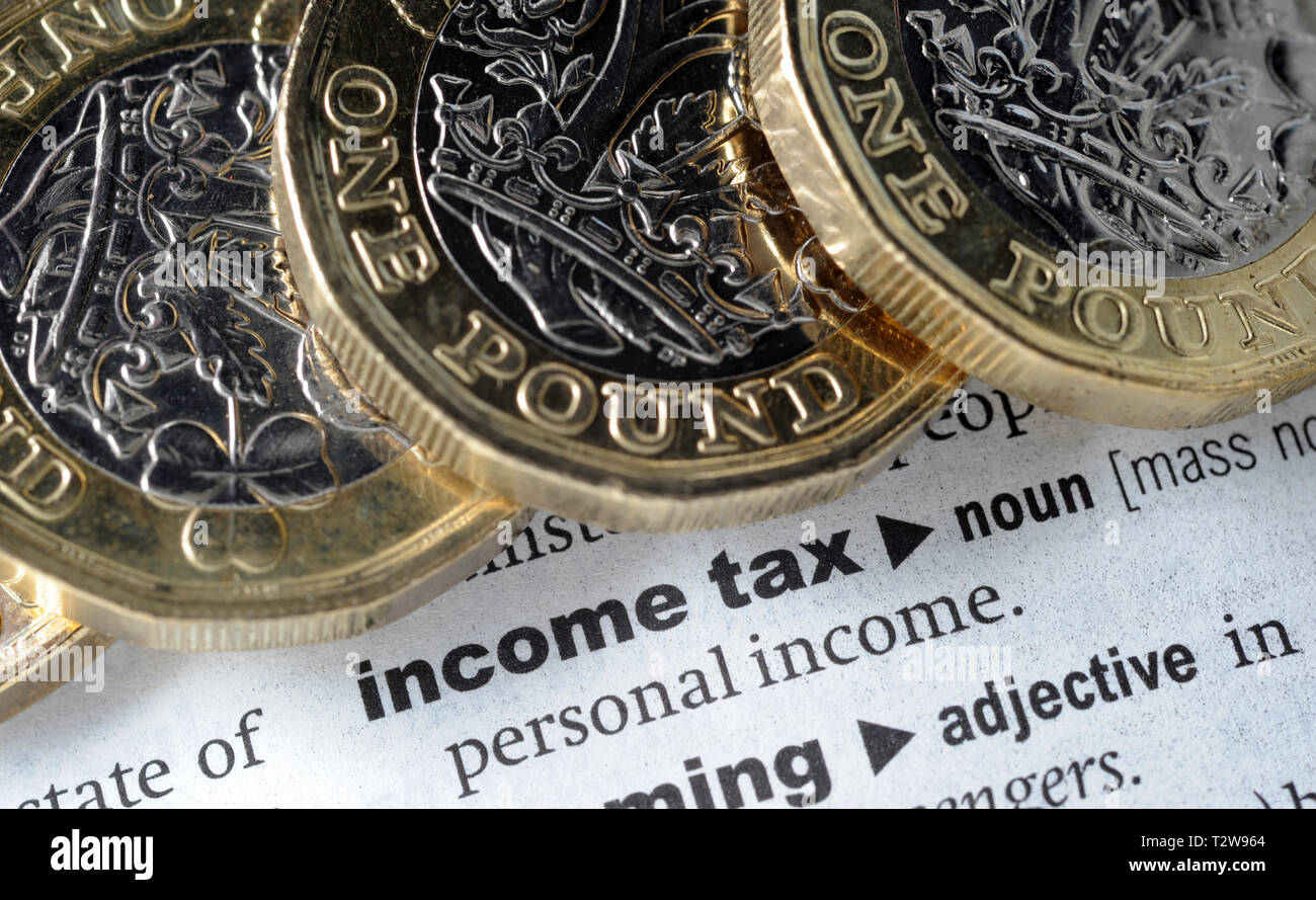 DICTIONARY DEFINITION OF INCOME TAX WITH ONE POUND COINS RE PENSIONS TAX HMRC ETC UK - Stock Image