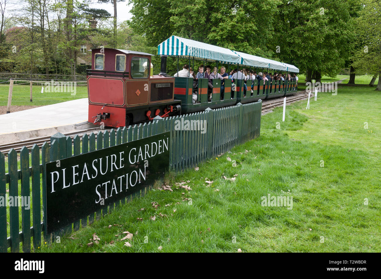 The small train named 'Sir Winston Churchill' with its carriages of visitors  leaving Pleasure Garden Station in the grounds of Blenheim Palace at Woo - Stock Image