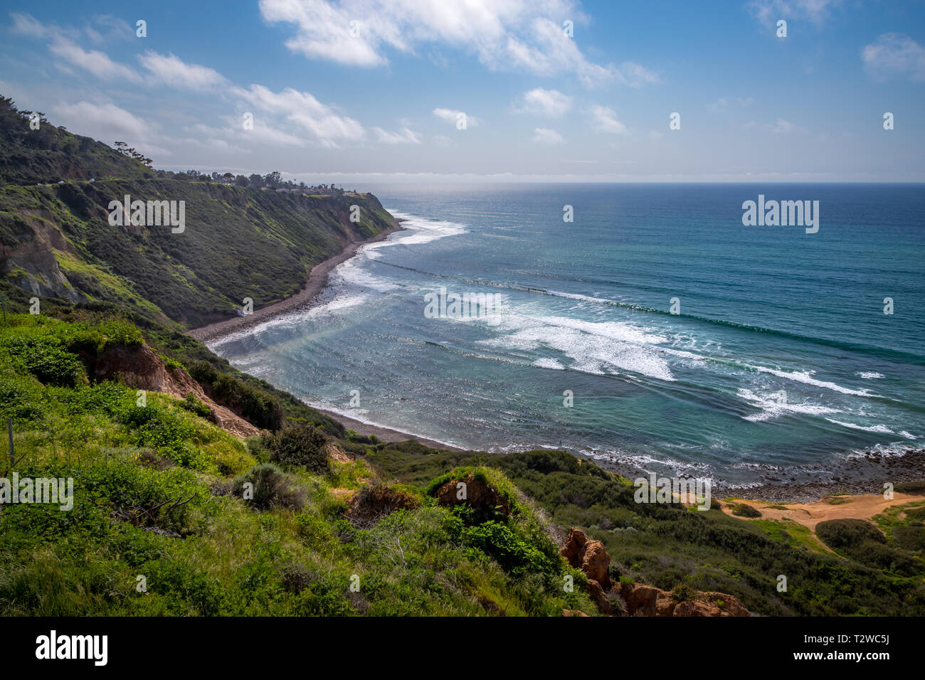 Scenic coastal view of tall cliffs of Bluff Cove covered with vegetation on a sunny spring day with  turquoise colored water and rocky beach, Blufftop - Stock Image