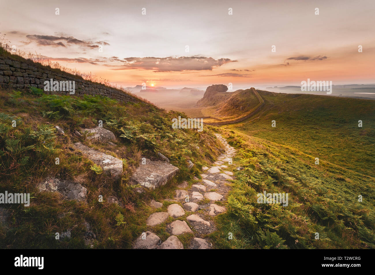 Dawn on path near Cuddy's Craig on Hadrian's Wall looking east towards Houseteads Craig and the rising sun. - Stock Image