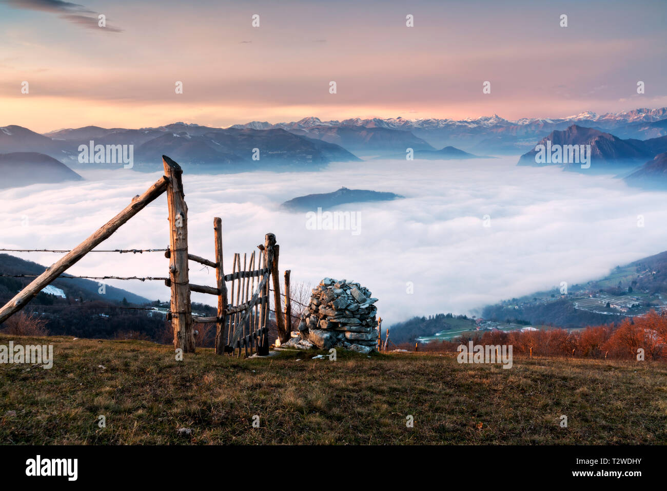 Iseo lake under the fog at sunset, Brescia province, Lombardy district in Italy, Europe. - Stock Image