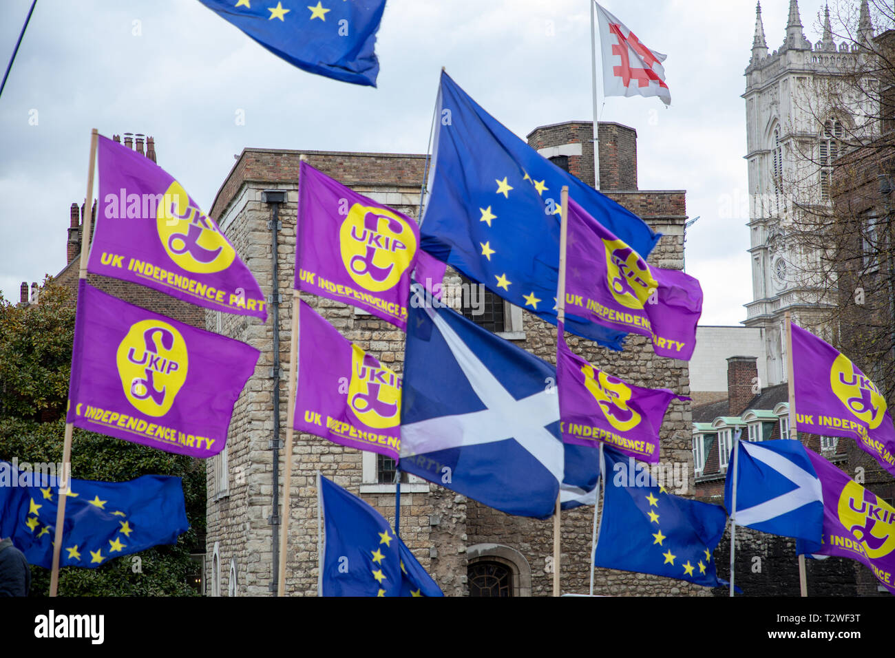 European Scottish and UKIP (UK Independence Party) flags wave outside Parliament, London, UK with Jewel Tower and Westminster Abbey in the background. - Stock Image