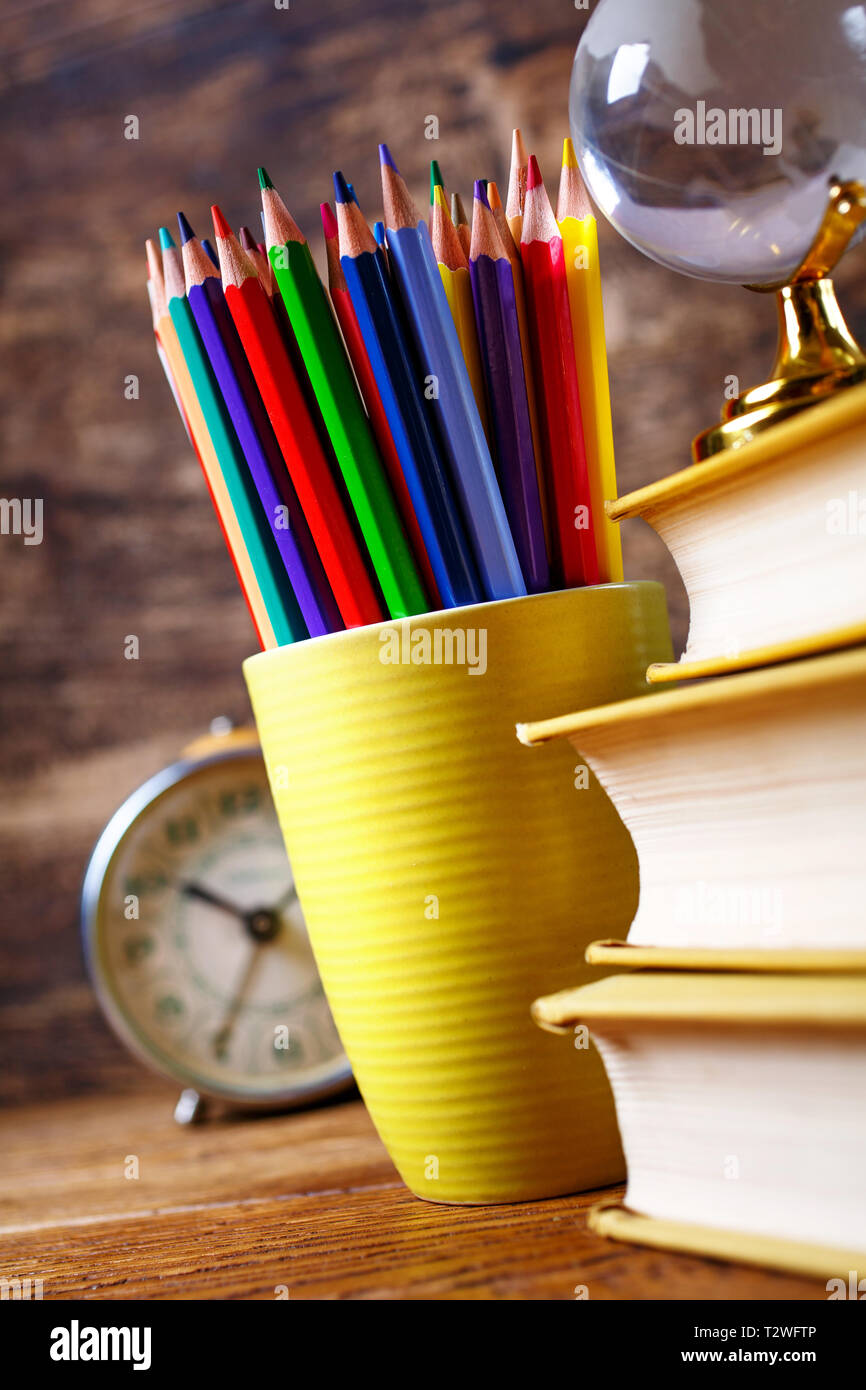Colored pencils in a glass next to books and watche. Concept of education or back to school. On a wooden background Stock Photo