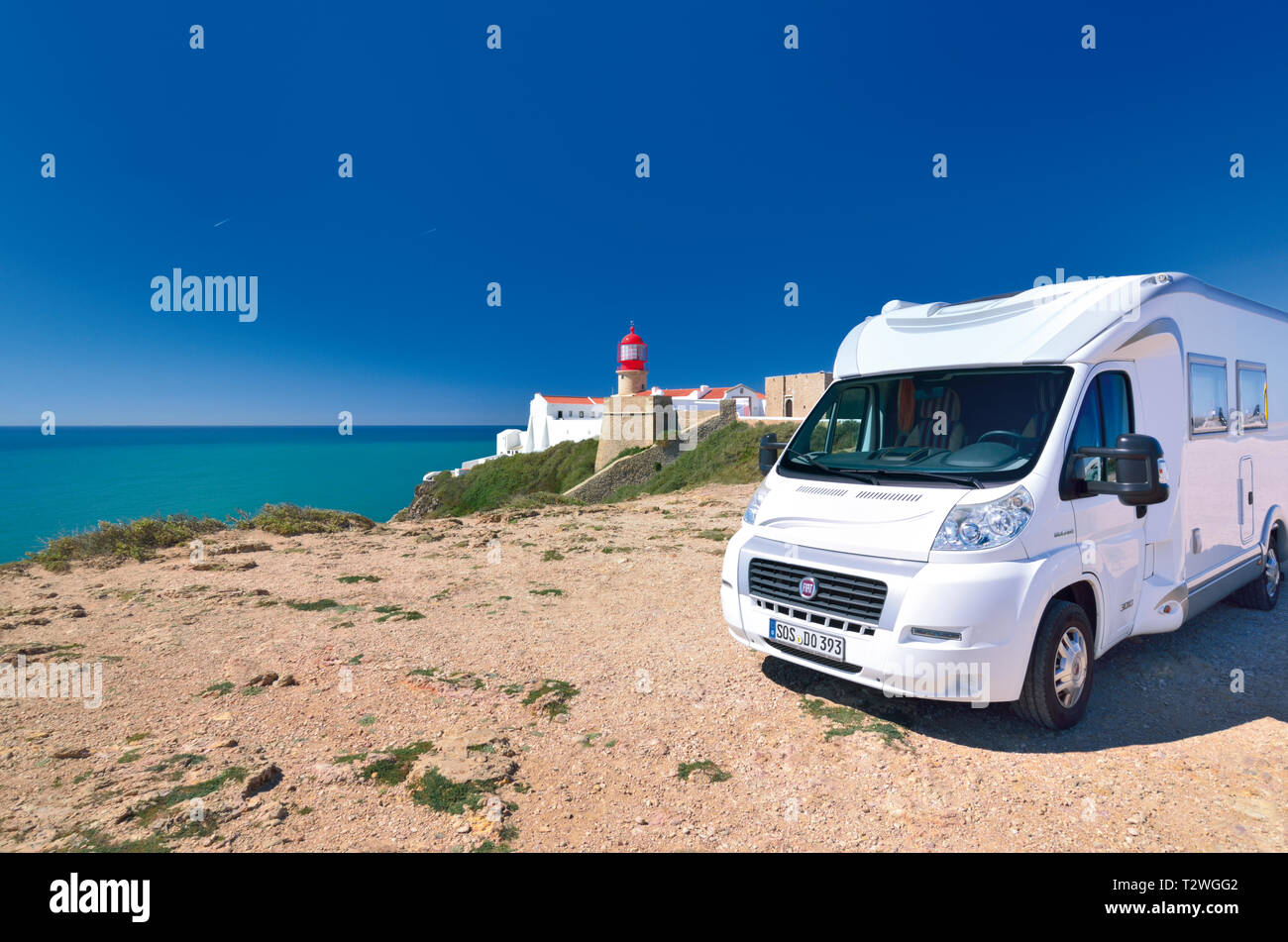 Motor home parking above cliffs with red lighthouse and green ocean view on a sunny day - Stock Image