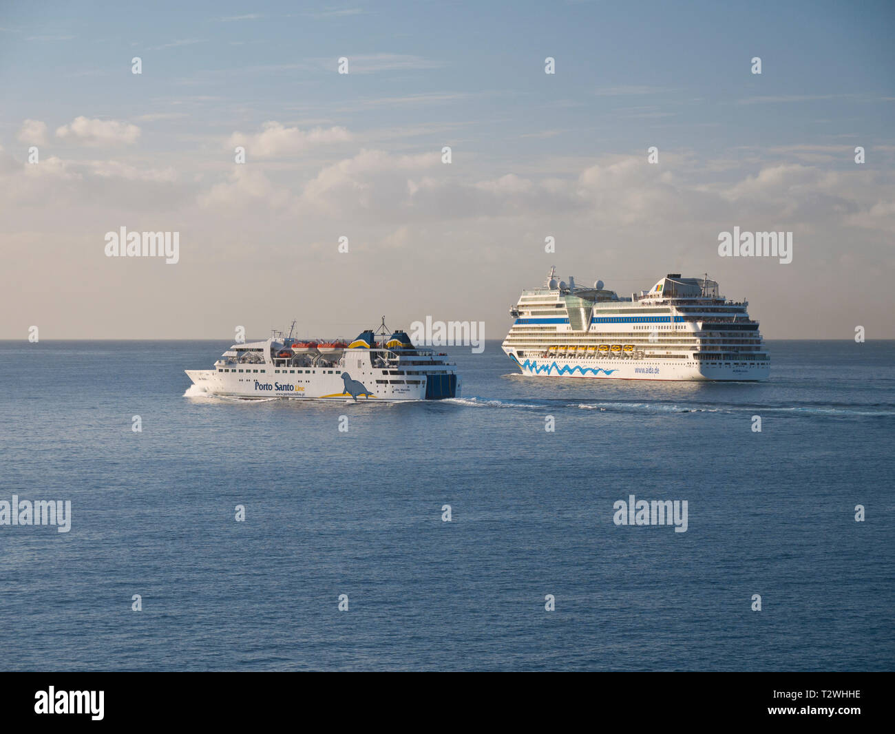 The Porto Santo Island Ferry and AIDA Stella cruise ship leaving Funchal port in Madeira after sunrise on a clear morning. - Stock Image