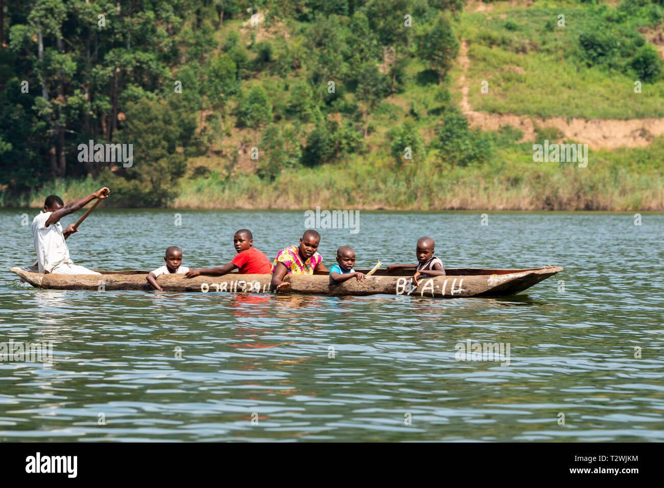 Boatman ferrying passengers in dugout canoe on Lake Bunyonyi in South West Uganda, East Africa - Stock Image