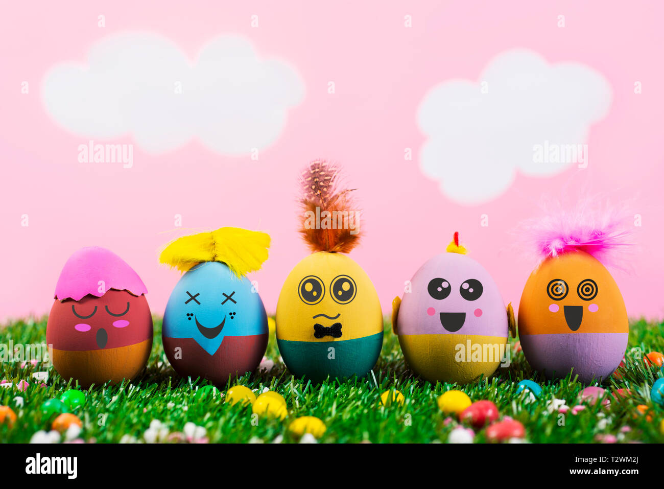 closeup of some handmade easter eggs, with cute and funny faces and hairstyles, on the grass with a pink sky with white clouds in the background - Stock Image