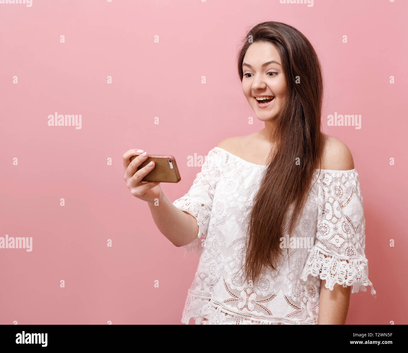 young woman happily looks into smartphone on pink background - Stock Image