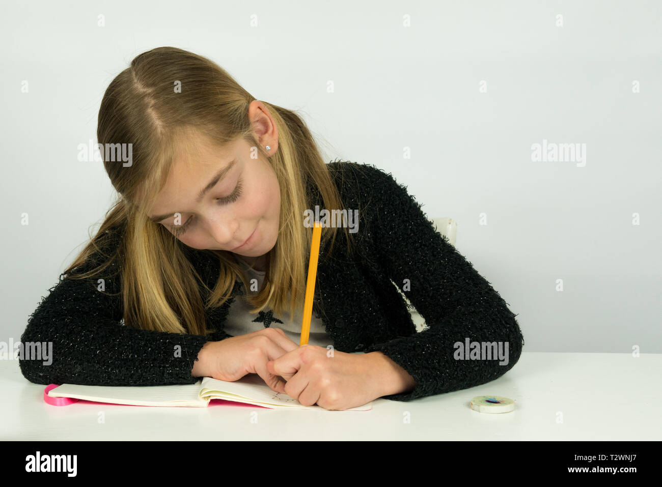Portrait of a cute girl is writing on her paper, doing homework - Stock Image