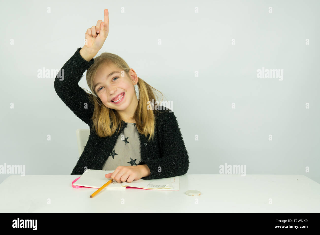 Cute girl is raising her hand in the classroom. She knows the answer the teacher asked - Stock Image