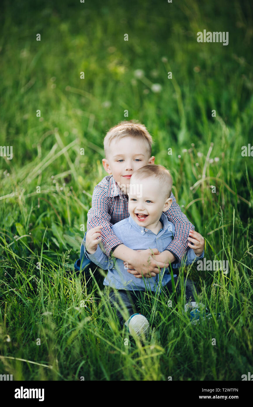 View of two little happy brothers wearing jeans and checked shirts, walking, playing in park, going forward. Boys wearing among green grass running an - Stock Image