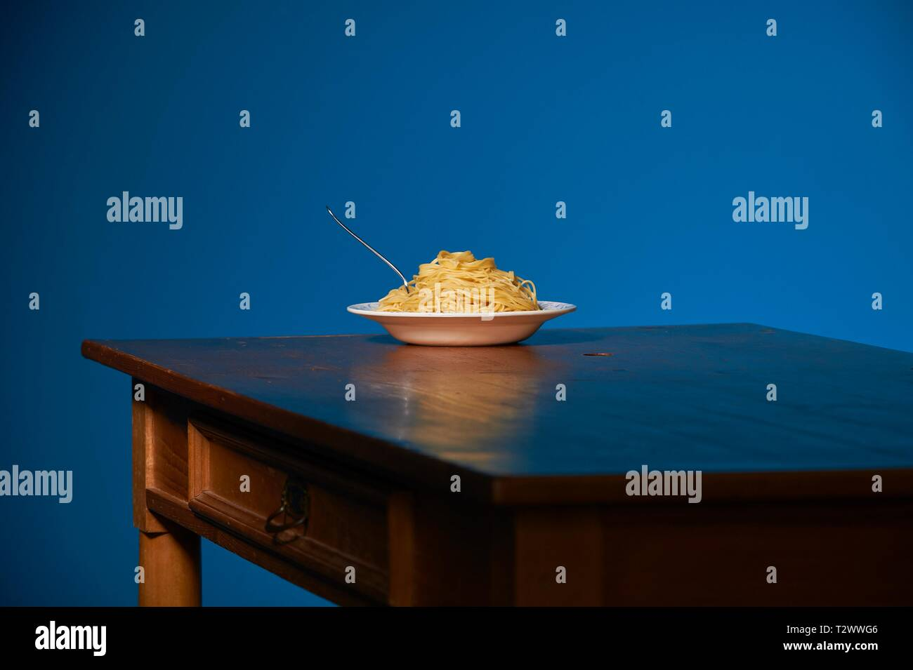 Eine Portion Spaghetti steht auf einenem Holztisch vor einer petrol farbenen Wand - Stock Image