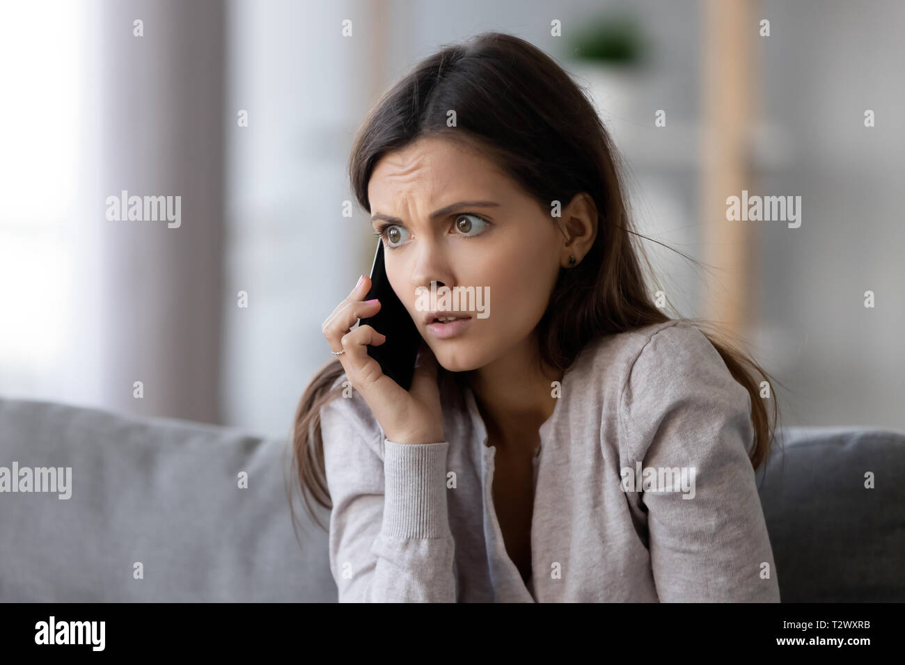 Shocked or scared young woman talking on mobile phone Stock Photo ...