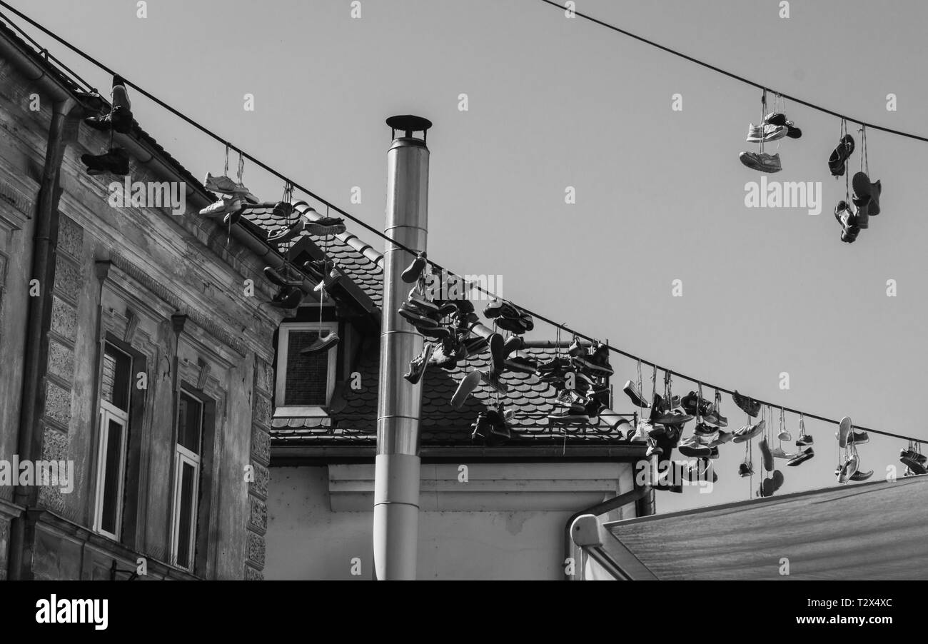 Black and white photo of shoes hanging on a wire in Ljubljana, Slovenia - Stock Image