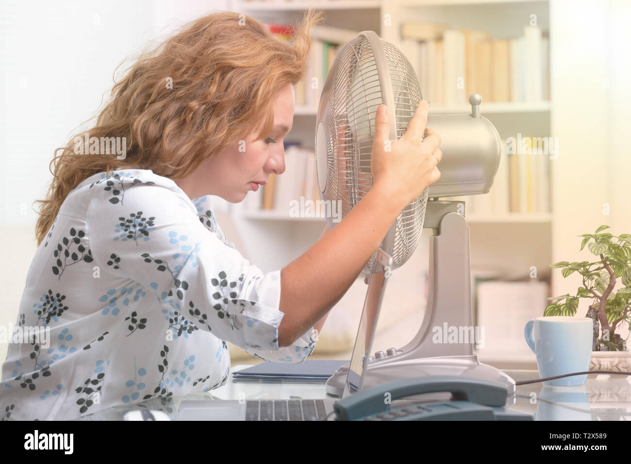 Woman suffers from heat while working in the office and tries to cool off by the fan - Stock Image