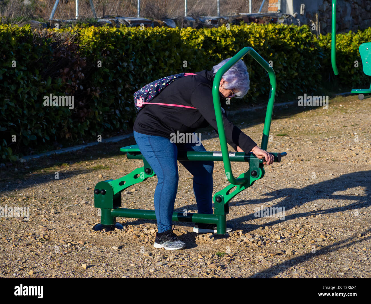A senior woman with white hair practicing gymnastics in a bio-healthy park Stock Photo