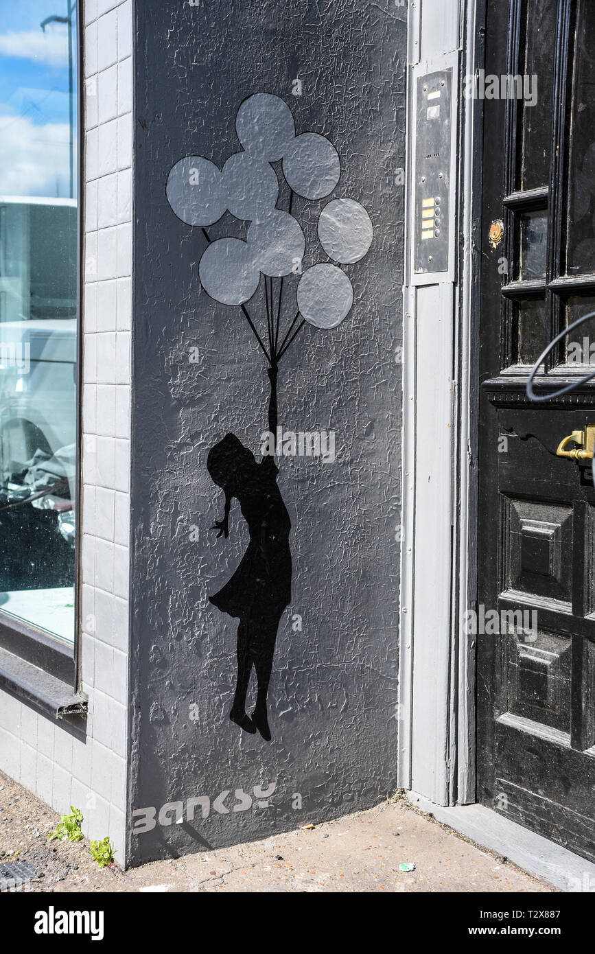 Banksy flying balloon girl wall decal on entrance to business premises, Westcliff, Essex, UK. Vinyl sticker - Stock Image