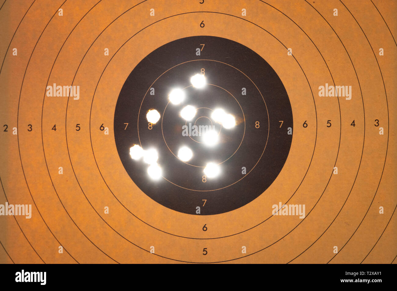 Close up of a shooting target with backlit bullet holes Stock Photo