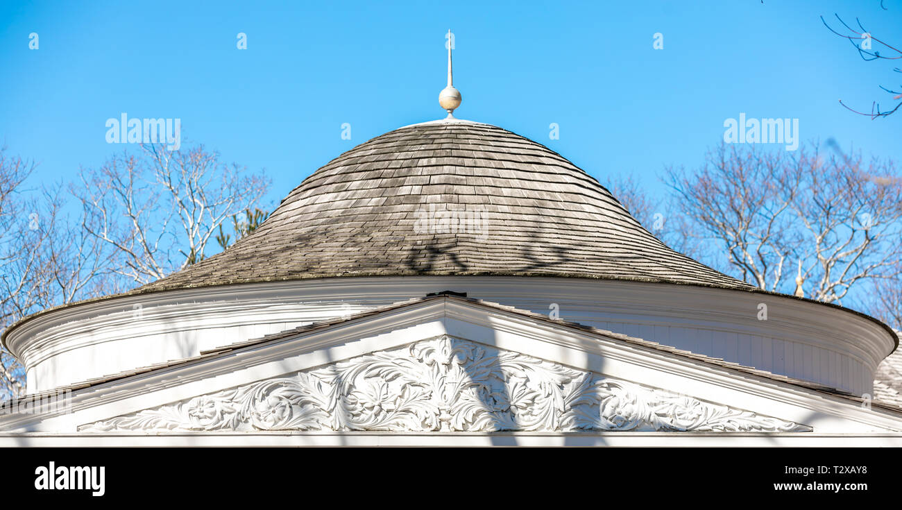 round roof element above an ornate pediment on the exterior of a house - Stock Image