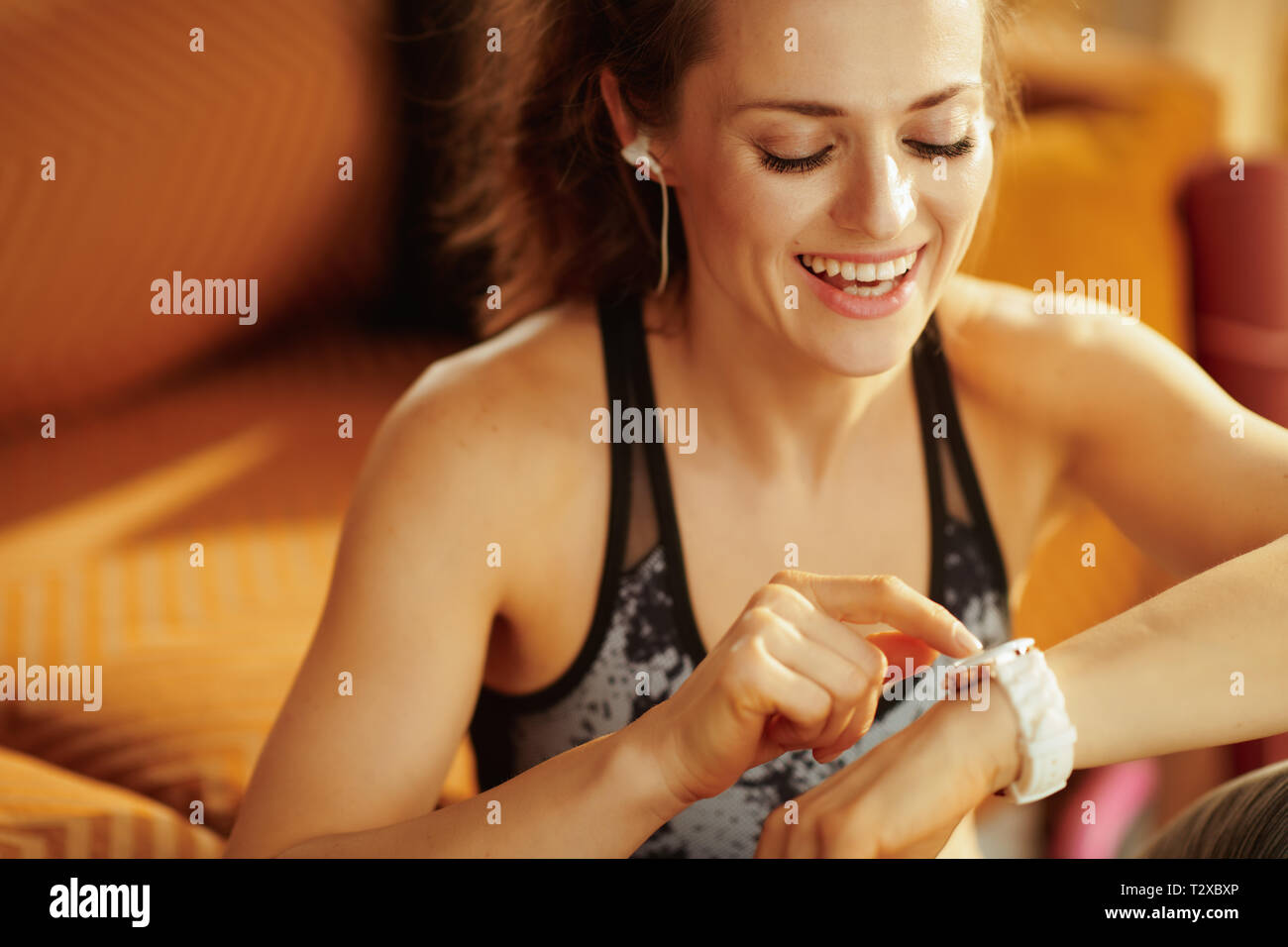 smiling young sports woman in sport clothes in the modern house using smart watch to track weight in fitness app. - Stock Image