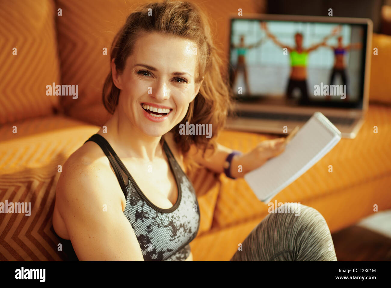 happy active woman in fitness clothes with notepad and pen taking notes while watching fitness tutorial on internet via laptop at modern home. Stock Photo