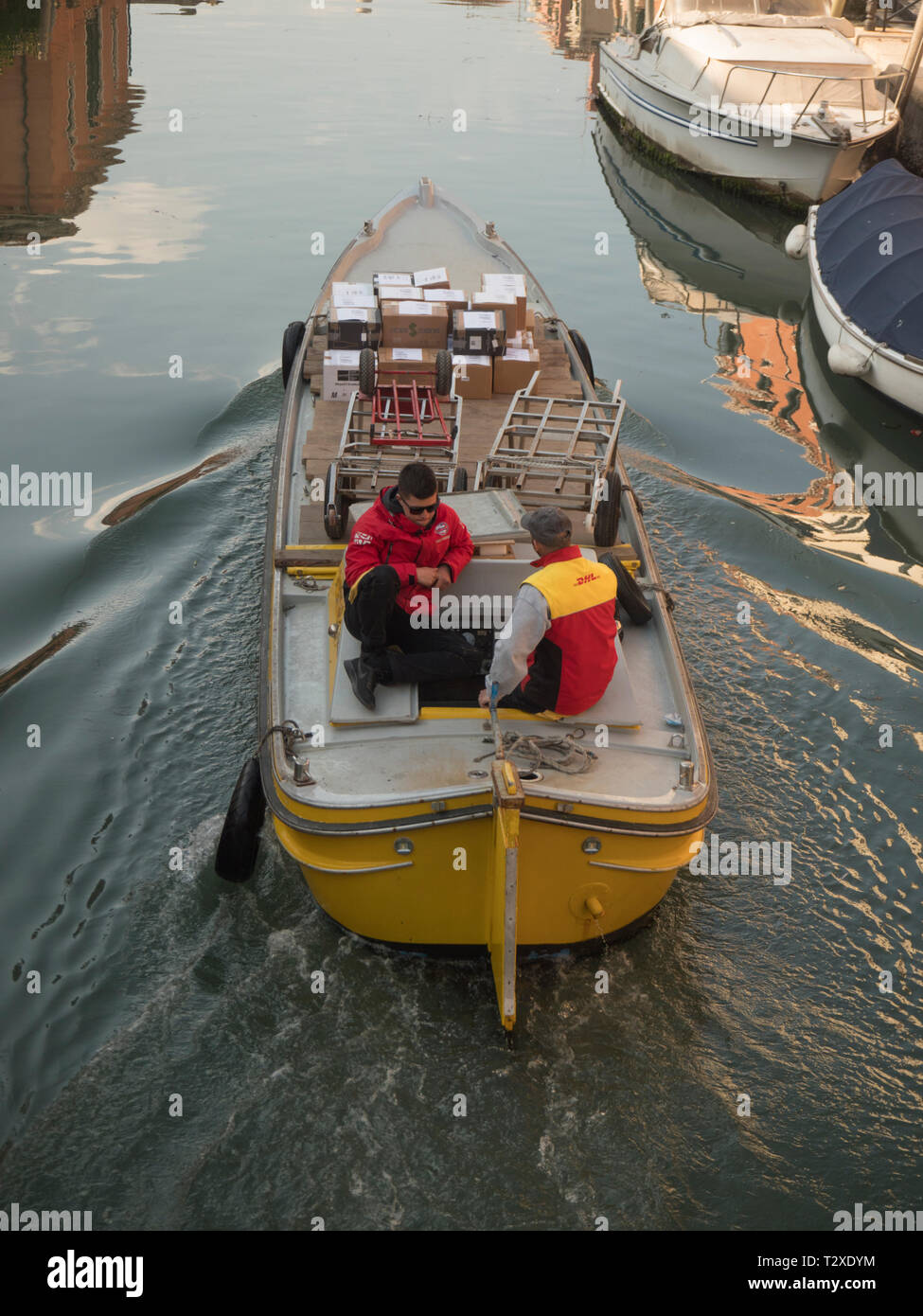 Waterborne canal delivery of mail and parcels by DHL in Venice - Stock Image