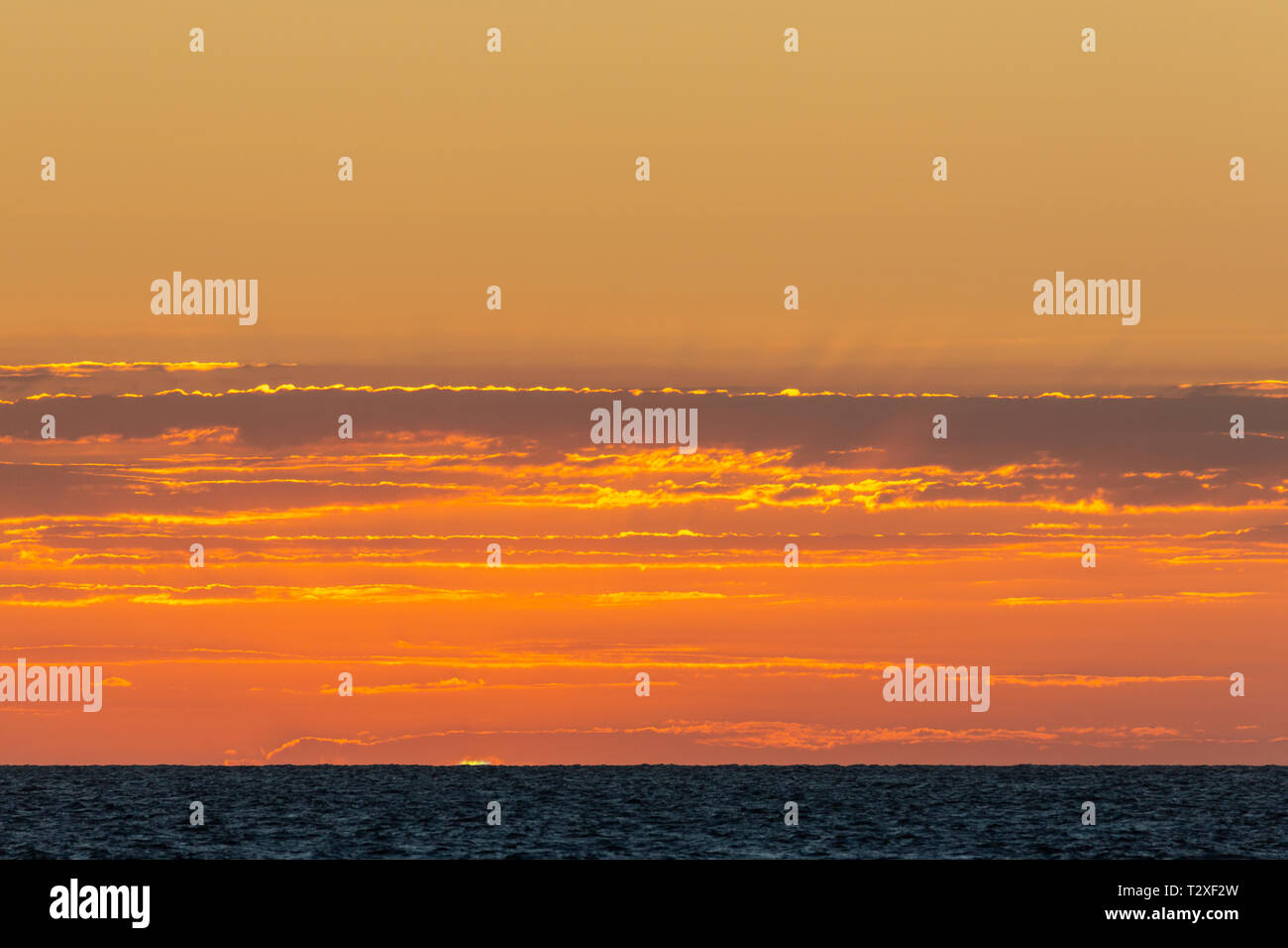 The famous Green Flash as the sun sets over the ocean as seen from the Silver Bank. - Stock Image