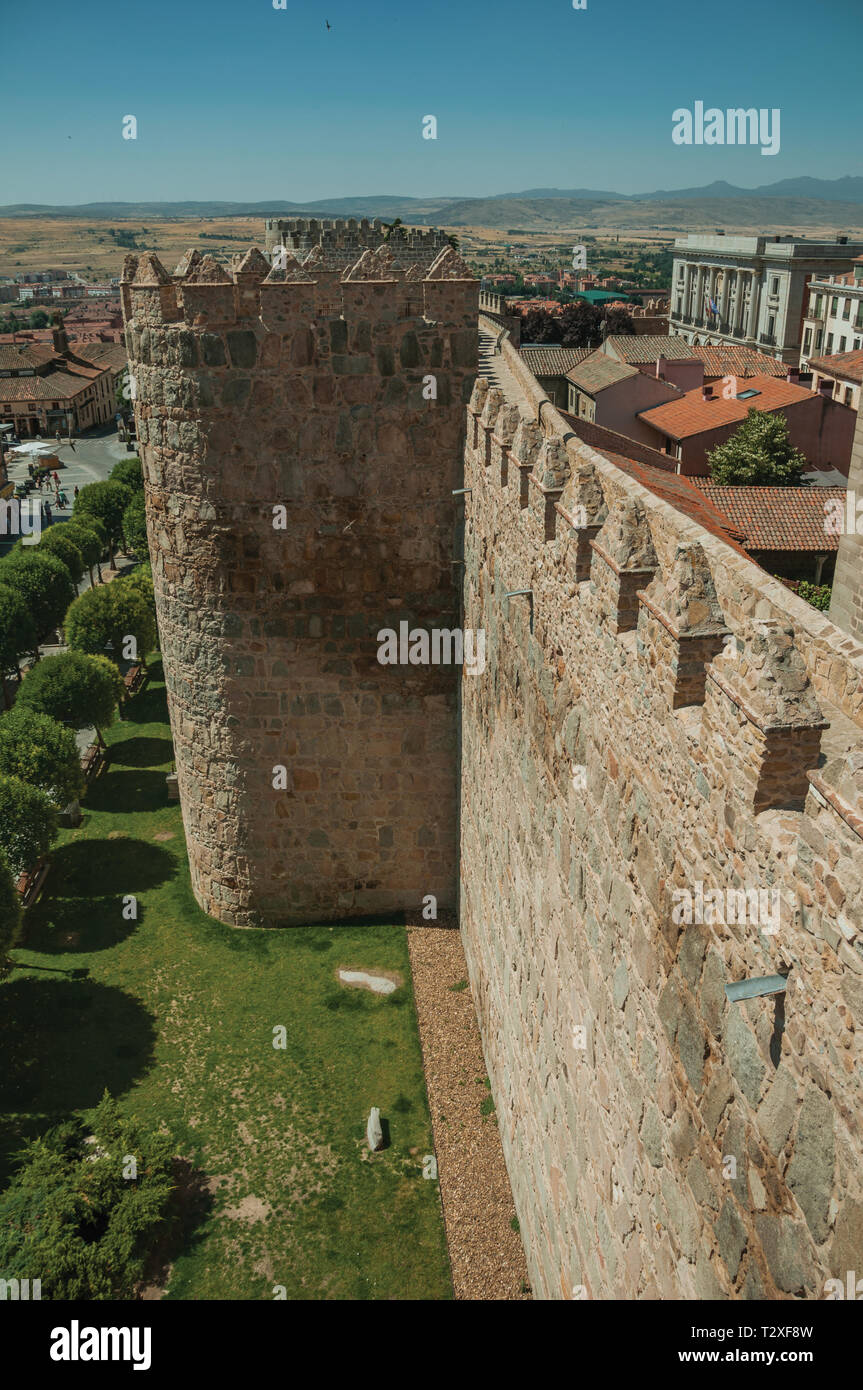 Stone thick wall with large tower encircling the town next to green garden at Avila. With an imposing wall around the gothic city center in Spain. - Stock Image